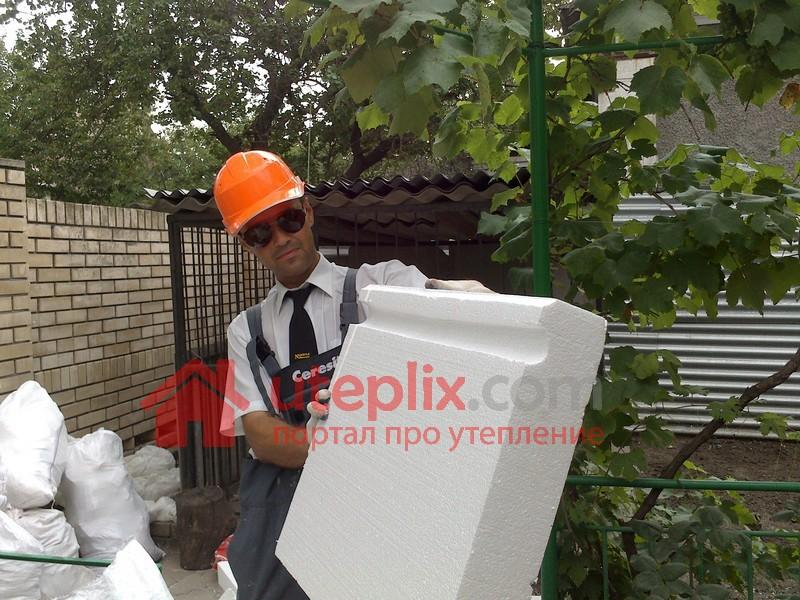 Работник с листом пенопласта